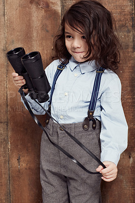 Buy stock photo Shot of a stylish young boy posing in the studio holding some binoculars