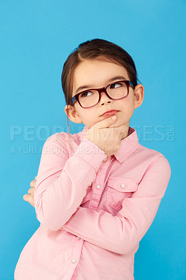 Buy stock photo A little girl holding her chin and looking up in a thoughtful expression