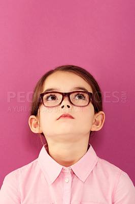 Buy stock photo A little girl wearing spectacles looking up against a pink background