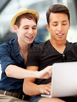 Buy stock photo Shot of a young man pointing at his friend's laptop