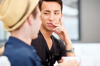 Buy stock photo Shot of a young man listening to his friend talk