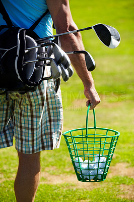Buy stock photo Cropped image of a golfer carrying a bucket of balls