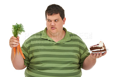 Buy stock photo An obese young man with a carrot in one hand and a slice of chocolate cake in the other and looking at the apple with a displeased expression against a white background