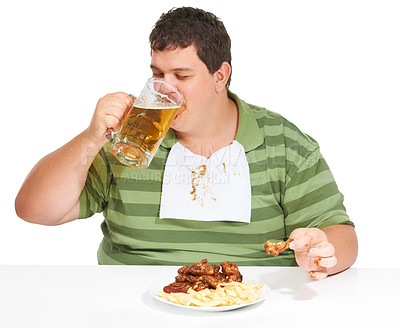 Buy stock photo An obese young man wearing a bib and drinking a beer with a plate of chicken wings and fries in front of him
