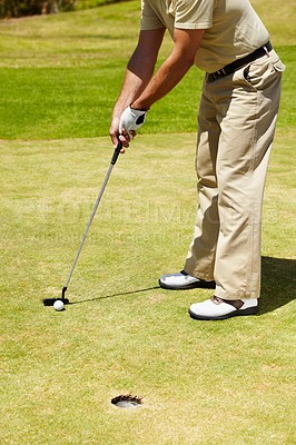 Buy stock photo A golfer putting on the green