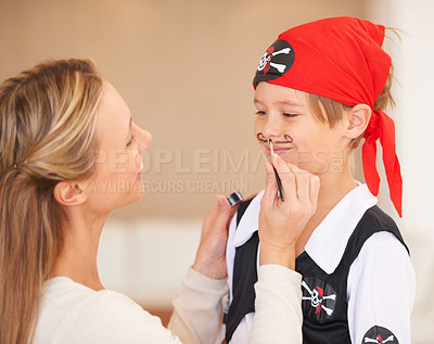 Buy stock photo A smiling boy standing in front of his mother who is painting a mustache on his face