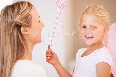 Buy stock photo Portrait of a smiling girl dressed up as a fairy and holding a wand standing infront of her mother