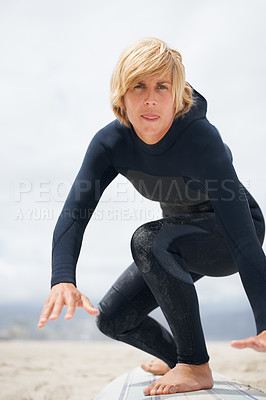 Buy stock photo Cropped shot of a female surfer standing on her surfboard