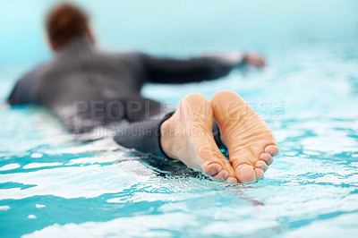 Buy stock photo Rearview shot of a man surfing in clear blue water