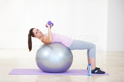 Buy stock photo Full length portrait of a young woman lying back on an exercise ball and lifting weights