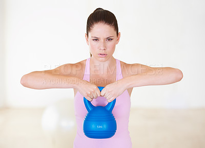 Buy stock photo Portrait of a determined-looking young woman lifting a dumbbell with both arms