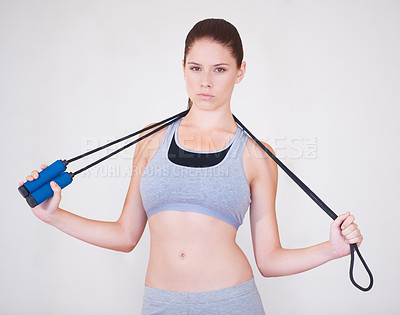 Buy stock photo Portrait of a serious-looking young woman holding a skipping rope over her shoulders