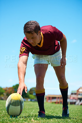 Buy stock photo Full length shot of a young rugby player setting up for a kick