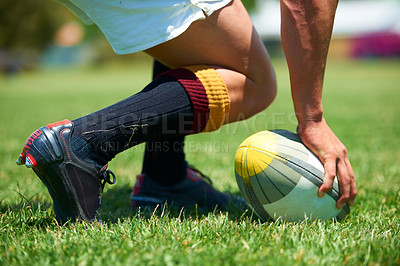 Buy stock photo Cropped shot of rugby player with his hand on the ball