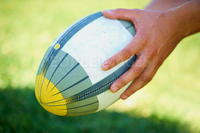 Buy stock photo Closeup shot of a rugby ball in a man's hand