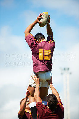 Buy stock photo Rearview shot of a young rugby player catching the ball during a lineout