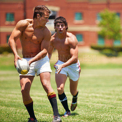 Buy stock photo Full length shot of two shirtless young rugby players going through a passing drill