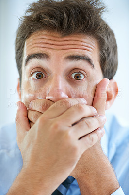 Buy stock photo Portrait of a young businessman with hands holding his mouth
