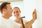 Woman with man hammering a nail into the wall