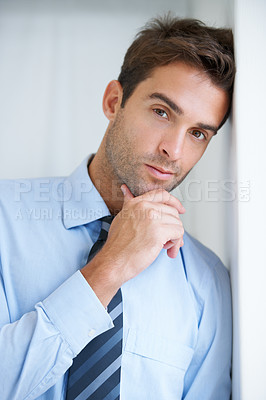 Buy stock photo Portrait of a businessman leaning against a wall with hand holding his chin