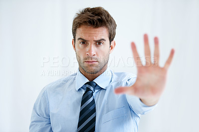 Buy stock photo Portrait of a businessman with a stern expression and holding up his hand in a stop motion