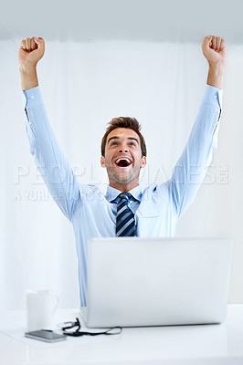 Buy stock photo A businessman sitting at his desk with his computer in front of him and cheering with his arms raised above his head