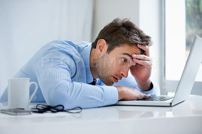 Buy stock photo A exhausted businessman falling asleep behind his laptop