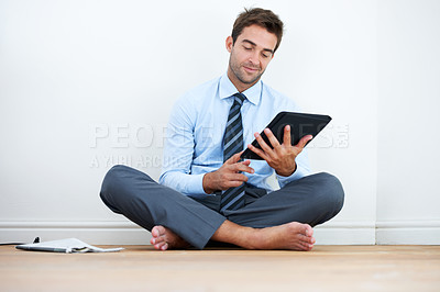 Buy stock photo A barefoot businessman sitting on the floor against a wall and using a digital tablet