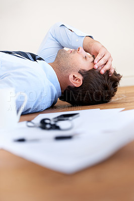 Buy stock photo A businessman lying on the floor with hand rested on his head and paperwork lying on the floor in front of him