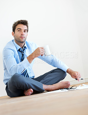 Buy stock photo A barefoot businessman sitting on the floor and having a cup of coffee with paperwork lying on the floor infront of him
