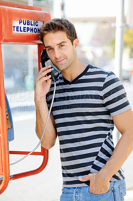 Buy stock photo A handsome young man standing casually with a hand in his pocket and using a public telephone