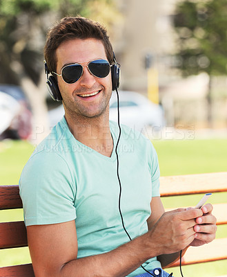 Buy stock photo A smiling young man wearing sunglasses sitting on a bench in a park and listening to music through his headphones