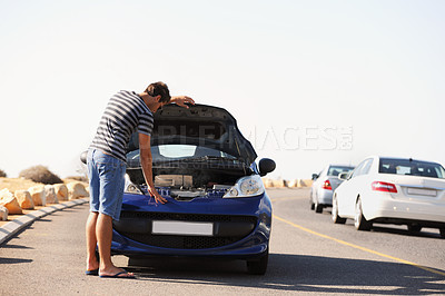 Buy stock photo A young man trying to fix his broken-down car on the side of the road