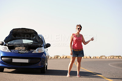 Buy stock photo A beautiful young woman standing with her broken-down car hitching a ride on the side of the road