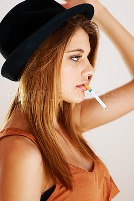 Buy stock photo A young trendy woman smoking a cigarette