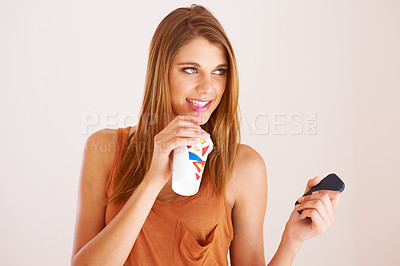 Buy stock photo A young woman drinking a soda while holding her cellphone