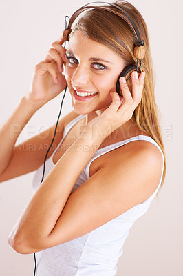 Buy stock photo A young woman listening to music on her headphones