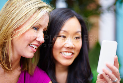 Buy stock photo Two female friends reading a text message together