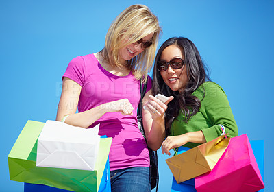 Buy stock photo Two young woman stopping to read a text message while out shopping