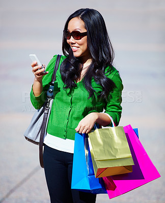 Buy stock photo A young woman sending a text message while on a shopping spree