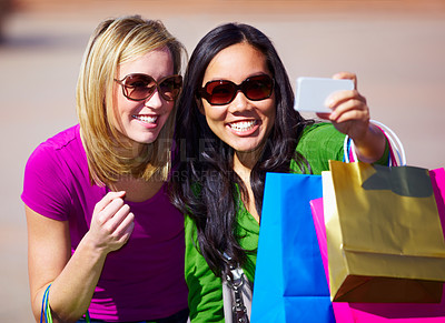 Buy stock photo Two woman taking a self portrait while out on a shopping spree