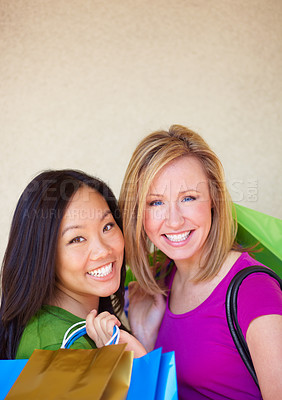 Buy stock photo Portrait of a two young woman looking happy to be out shopping