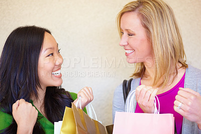 Buy stock photo Two young woman shopping together and smiling happily