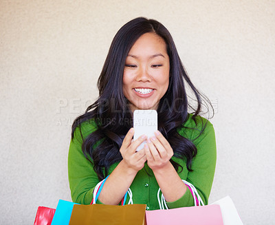 Buy stock photo Closeup of a young asian woman reading a text message while shopping