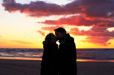 Buy stock photo Silouehette of a couple kissing on the beach at sunset
