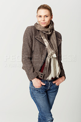 Buy stock photo Cropped studio portrait of a an attractive young woman standing with her hands in her pockets