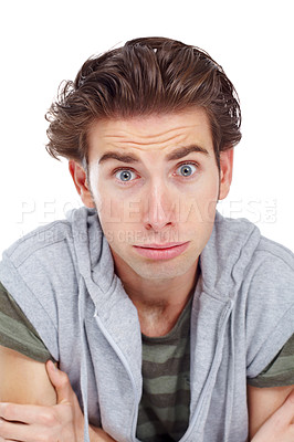 Buy stock photo Young man holding his arm and looking at the camera with an apprehensive expression