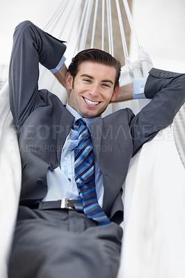 Buy stock photo A young businessman lying on a hammock