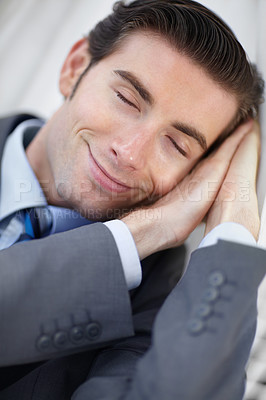 Buy stock photo A young businessman fast asleep and smiling