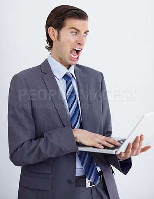 Buy stock photo A crazy businessman screaming at his laptop screen as it stalls once again